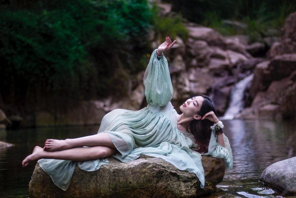 менструални чашки жена лежи върху камани пред река